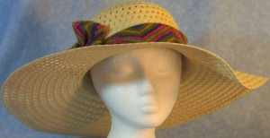 Wide brim hat is tan, paper braid shown with brightly, colored band with V's design