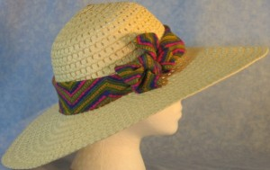 Wide brim hat is tan, paper braid shown with brightly, colored band with V's design-side