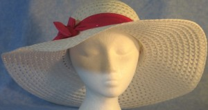 Wide brim hat is white, paper braid shown with sparkly, pink band