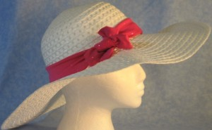 Wide brim hat is white, paper braid shown with sparkly, pink band-side