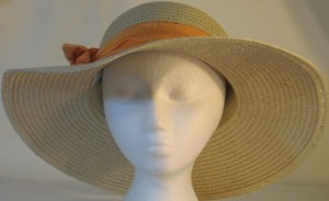 Wide brim hat is tan with sequins shown with orange band