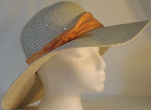 Wide brim hat is tan with sequins shown with orange band-side