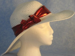 Wide brim hat is white with sequins shown with shiny, red band-side