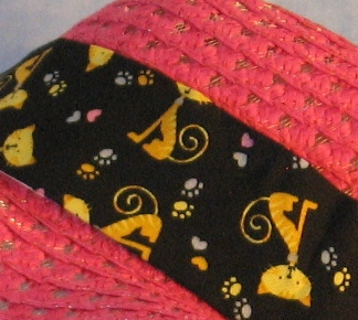 Wide brim hat is pink, paper braid shown with black cat band-closeup