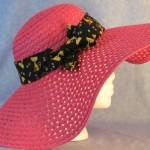 Wide brim hat is pink, paper braid shown with black cat band-side