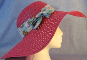 Wide brim hat is pink, paper braid shown with blue cat band-side