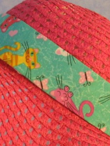 Wide brim hat is pink, paper braid shown with green cat band-closeup