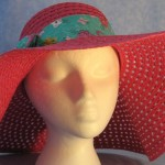 Wide brim hat is pink, paper braid shown with green cat band-front