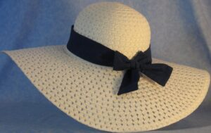 Wide brim hat is white, paper braid shown with blue with black polka dots band-back