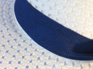 Wide brim hat is white, paper braid shown with blue with black polka dots band-closeup