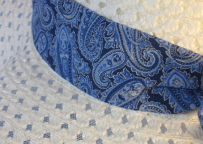 Wide brim hat is white, paper braid shown with blue paisley band-closeup