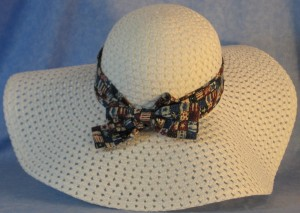 Wide brim hat is white, paper braid shown with patriotic, small flags band-back