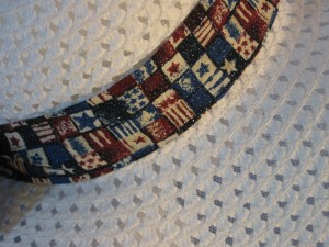 Wide brim hat is white, paper braid shown with patriotic, small flags band-closeup