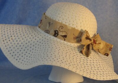 Wide brim hat is white, paper braid shown with tan cat band-side