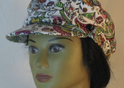 Fisherman Cap in Purple Yellow Green Flowers Paisley Balls Outlined in Black on White Flannel - front left